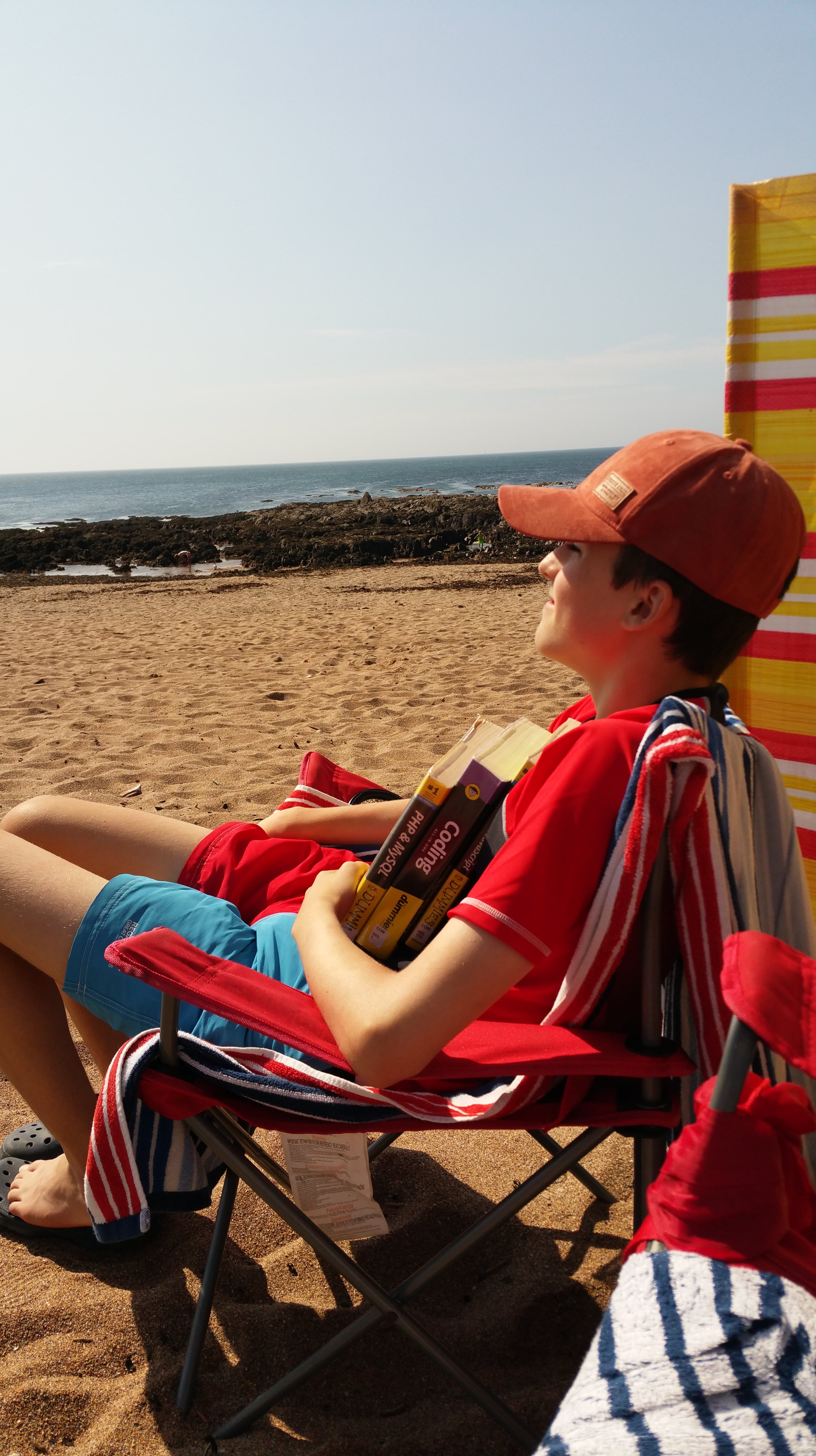 Me with my coding books on a beach in Devon